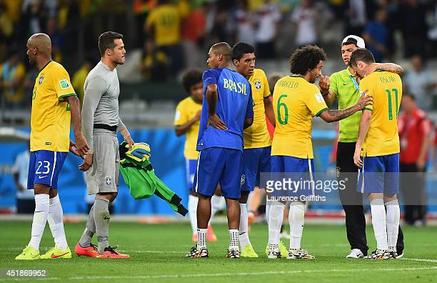 Oscar of Brazil is consoled by Marcelo and Thiago Silva as goalkeeper Julio Cesar looks on after a 71 defeat to Germany during the 2014 FIFA World...