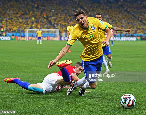 Oscar of Brazil is tripped up by Sime Vrsaljko of Croatia in the second half during the 2014 FIFA World Cup Brazil Group A match between Brazil and...