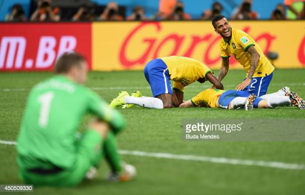 Oscar of Brazil lies on the ground celebrating his goal with Ramires and Dani Alves as Stipe Pletikosa of Croatia sits looking on in the second half...