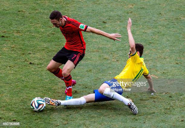 Oscar of Brazil tackles Miguel Layun of Mexico during the 2014 FIFA World Cup Brazil Group A match between Brazil and Mexico at Castelao on June 17...
