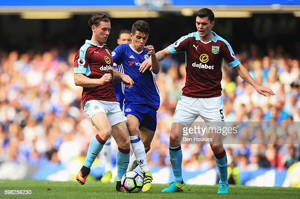 Oscar of Chelsea attempts to get past Jon Flanagan of Burnley and Michael Keane Eof Burnley during the Premier League match between Chelsea and...