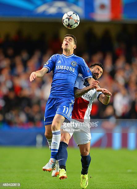 Oscar of Chelsea jumps to beat Ezequiel Lavezzi of PSG to the ball during the UEFA Champions League Quarter Final second leg match between Chelsea...