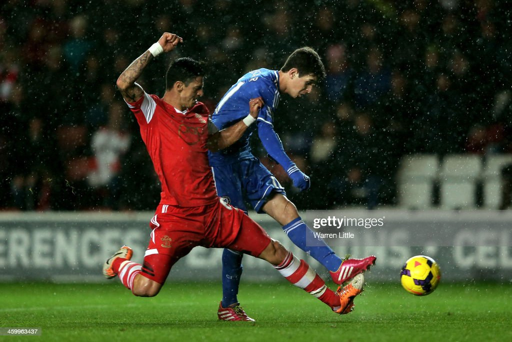 Oscar of Chelsea scores his team's third goal despite the tackle from Jose Fonte of Southampton during the Barclays Premier League match between Southampton and Chelsea at St Mary's Stadium on January 1, 2014 in Southampton, England.