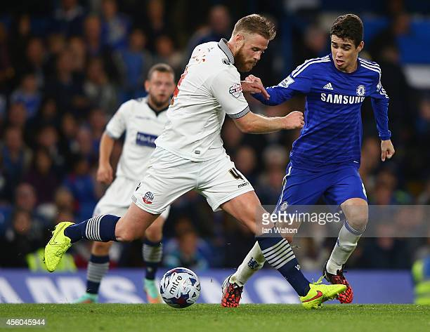 Oscar of Chelsea tries to tackle Matt Mills of Bolton Wanderers during the Capital One Cup Third Round match between Chelsea and Bolton Wanderers at...