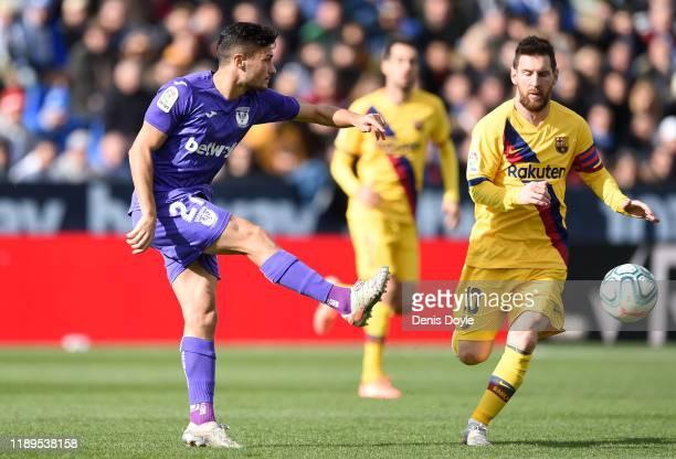 Oscar of Leganes battles for possession with Lionel Messi of FC Barcelona during the La Liga match between CD Leganes and FC Barcelona at Estadio...