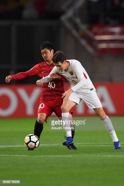 Oscar of Shanghai SIPG and Mitsuo Ogasawara of Kashima Antlers compete for the ball during the AFC Champions League Round of 16 first leg match...