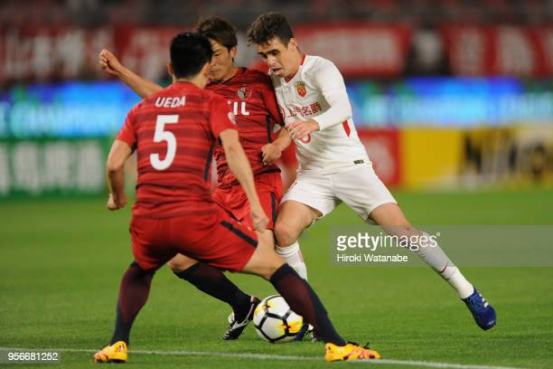 Oscar of Shanghai SIPG takes on Ryota Nagaki and Naomichi Ueda of Kashima Antlers during the AFC Champions League Round of 16 first leg match between...