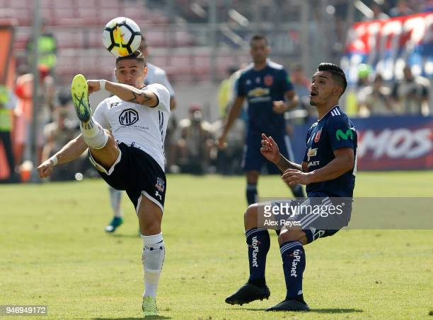 Oscar Opazo of Colo Colo fights for the ball with Lorenzo Reyes of U de Chileduring a match between U de Chile and Colo Colo as part of Torneo...