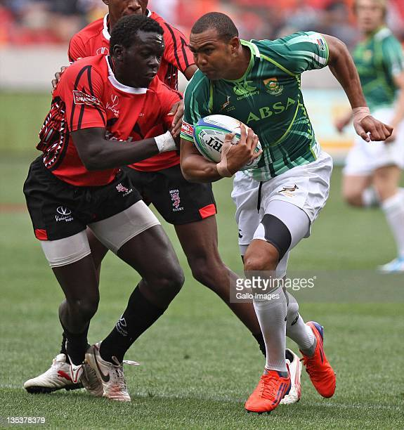 Oscar Ouma of Kenya moves in to tackle Cornal Hendricks of South Africa during day 1 of the 2011 IRB PE Sevens at Nelson Mandela Bay Stadium on...