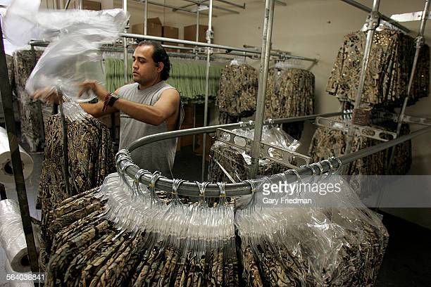 Oscar Perez wraps womens clothes at Holy Camp Clothing located in downtown Los Angeles Some of the employees of owner Sam Hong receive minimum wage...