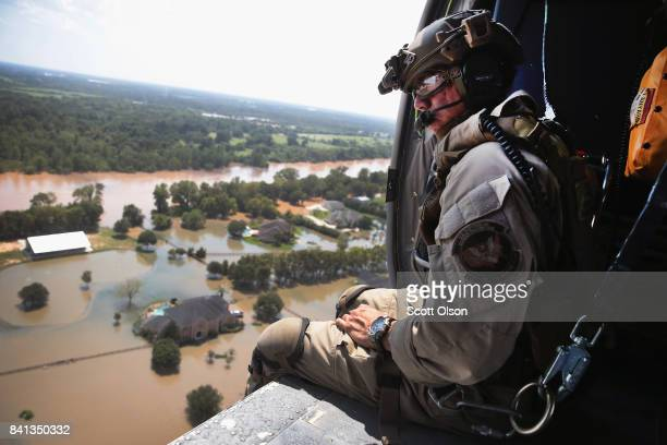Oscar Peru of US Customs and Border Protection searches for flood victims from a helicopter after torrential rains pounded the area following...