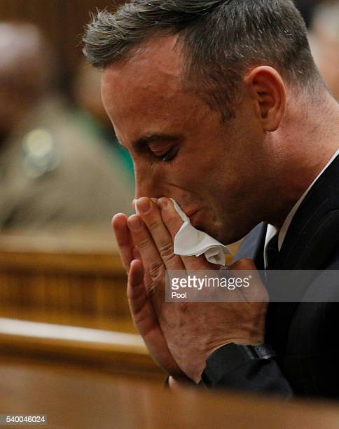 Oscar Pistorius cries as he sits inside the dock at the high court in Pretoria for his sentencing hearing at the high court in Pretoria on June 14,...