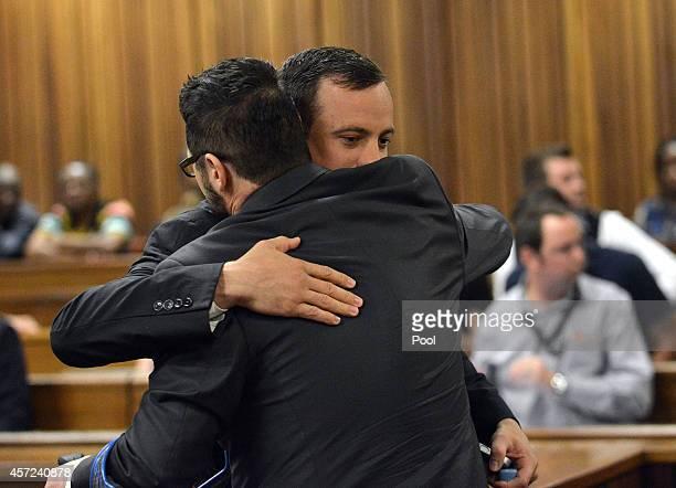 Oscar Pistorius greets his brother Carl Pistorius at the Pretoria High Court on October 15 in Pretoria South Africa Judge Thokozile Masipa found...