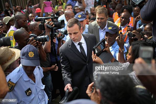 Oscar Pistorius is surrounded by police and media as he leaves North Gauteng High Court after the fifth day of his trial on March 7, 2014 in...