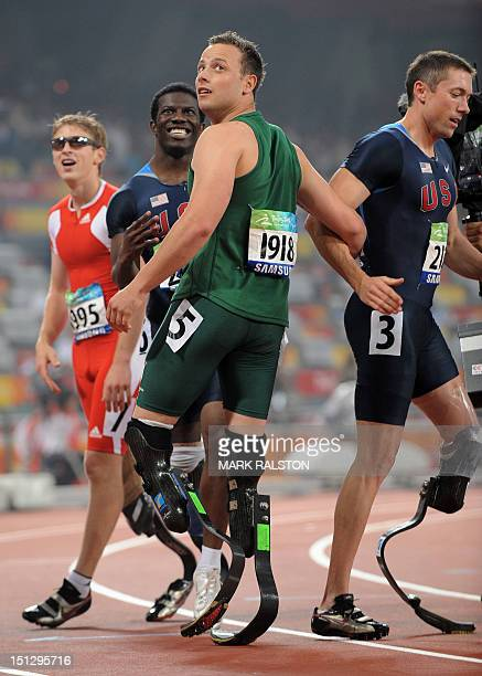 Oscar Pistorius of South Africa checks his time as he celebrates winning the final of the men's 100 metre T44 classification race at the 2008 Beijing...
