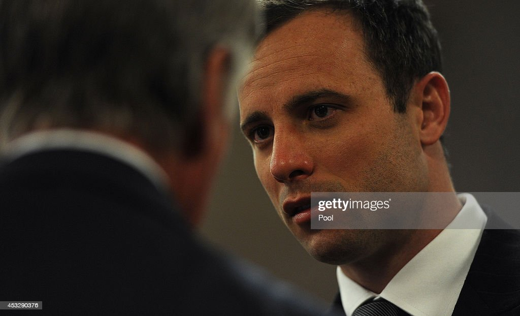 Oscar Pistorius speaks to Brian Webber, a member of his defence team, in the Pretoria High Court on August 7, 2014, in Pretoria, South Africa. Oscar Pistorius stands accused of the murder of his girlfriend, Reeva Steenkamp, on February 14, 2013. This is Pistorius' official trial, the result of which will determine the paralympian athlete's fate.