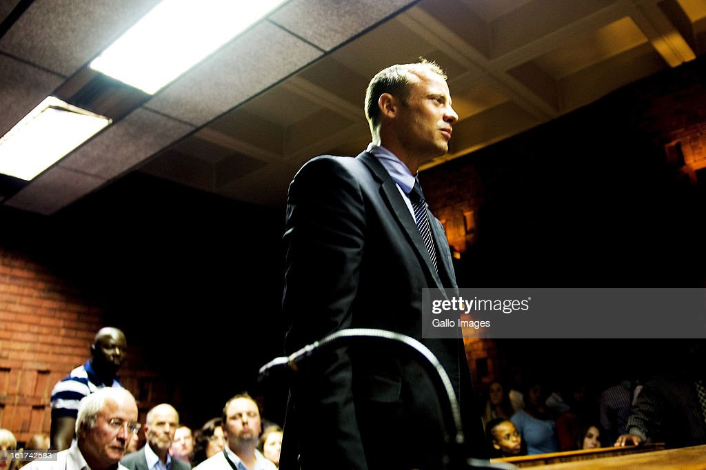 Oscar Pistorius stands for the charges during the Pretoria Magistrate court hearing on February 15, 2013, in Pretoria, South Africa. Oscar Pistorius stands accused of murder after shooting girlfriend Reeva Steenkamp on the morning of February 14, 2013. His bail hearing has been postponed until February 19, 2013, with prosecutors stating they will pursue a charge of premeditated murder against him.