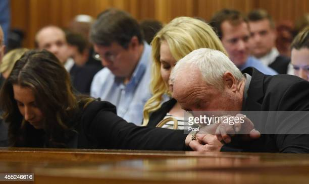 Oscar Pistorius's father Henke Pistorius kisses the hand of his daughter Aimee Pistorius while part of the judgment is handed down in the Pretoria...