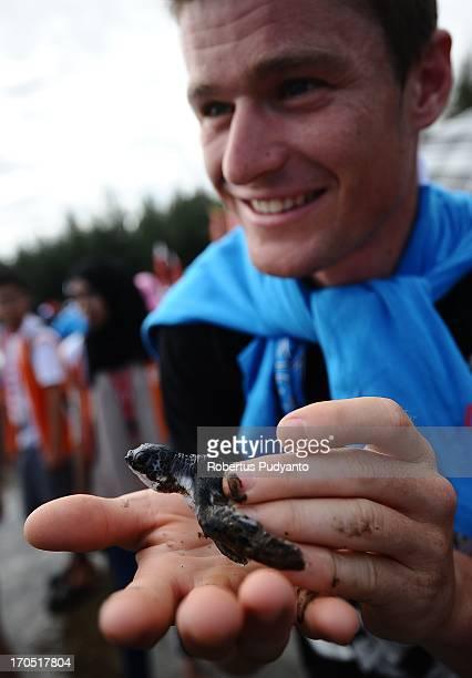 Oscar Pujol Munoz, Spanis rider from Polygon Sweet Nice Cycling Team released baby sea turtles in Air Manis Beach, Padang, West Sumatra, Indonesia....