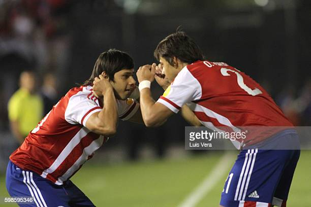 Oscar Romero of Paraguay celebrates with his teammate Angel Romero after scoring the first goal of his team during a match between Paraguay and Chile...