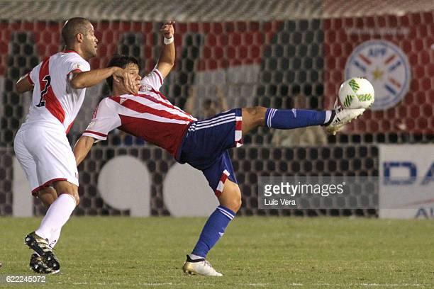 Oscar Romero of Paraguay kicks the ball while defended by Alberto Rodriguez of Peru during a match between Paraguay and Peru as part of FIFA 2018...