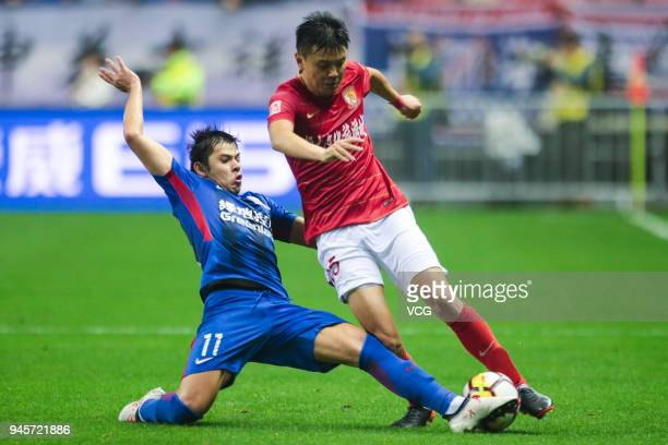 Oscar Romero of Shanghai Shenhua and Zou Zheng of Guangzhou Evergrande compete for the ball during the 2018 Chinese Super League 6th round match...