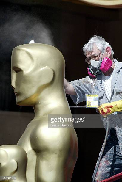 Oscar statues are given one final coat of spray paint the day before the Academy Awards at Hollywood and Highland on February 28 2004 in Hollywood...
