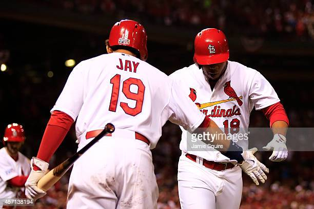 Oscar Taveras of the St Louis Cardinals celebrates hitting a solo home run in the seventh inning against the San Francisco Giants with Jon Jay during...