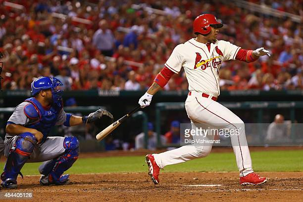 Oscar Taveras of the St Louis Cardinals hits an RBI single in the eighth inning against the Chicago Cubs at Busch Stadium on August 30 2014 in St...