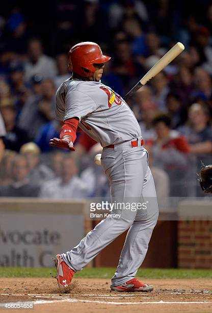 Oscar Taveras of the St Louis Cardinals is hit by a pitch during the second inning against the Chicago Cubs at Wrigley Field on September 24 2014 in...