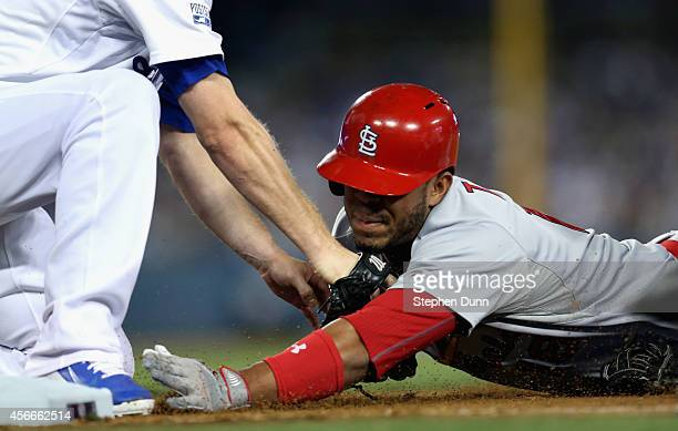 Oscar Taveras of the St Louis Cardinals slides safely back into first base to beat pitcher JP Howell of the Los Angeles Dodgers in the eighth inning...