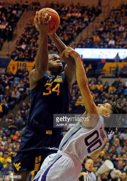 Oscar Tshiebwe of the West Virginia Mountaineers drives against Mike McGuirl of the Kansas State Wildcats at the WVU Coliseum on February 1 2020 in...
