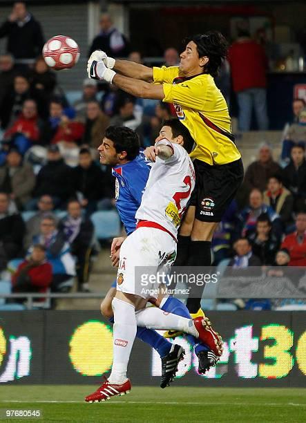 Oscar Ustari of Getafe fists the ball against Aritz Aduriz of Mallorca and Miguel Torres of Getafe during the La Liga match between Getafe and...