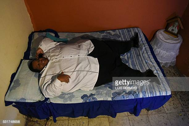 Oscar Vasquez Morales considered the most obese male of the country with about 400 kg speaks through his mobile on May 16 2016 in Cali Colombia...