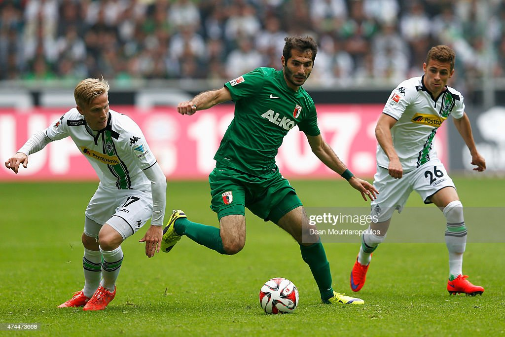 Oscar Wendt (L) and Thorgan Hazard (R) of Borussia Moenchengladbach chase Halil Altintop of FC Augsburg during the Bundesliga match between Borussia Moenchengladbach and FC Augsburg held at Borussia Park Stadium on May 23, 2015 in Moenchengladbach, Germany.