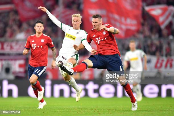 Oscar Wendt of Borussia Monchengladbach battles for possession with Niklas Suele of Bayern Munich during the Bundesliga match between FC Bayern...