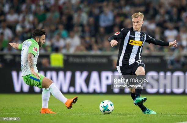 Oscar Wendt of Borussia Monchengladbach is attacked by Renato Steffen of VfL Wolfsburg during the Bundesliga match between Borussia Moenchengladbach...