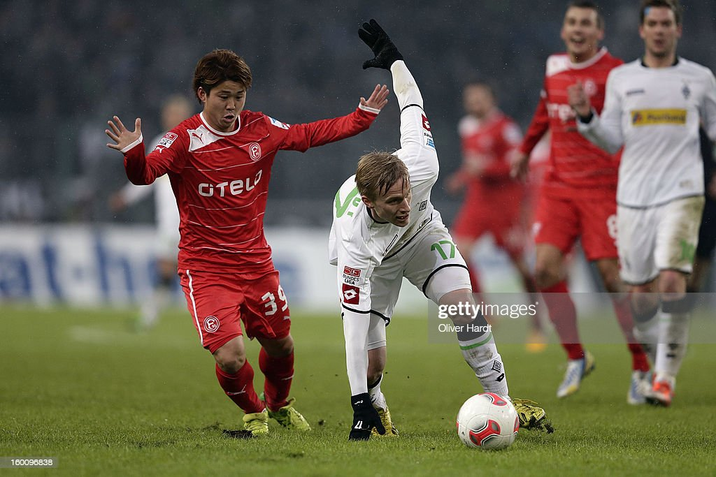 Oscar Wendt (R) of Gladbach and Genki Omae (L) of Duesseldorf battle for the ball during at Bundesliga match between VfL Borussia Moenchengladbach v Fortuna Duesseldorf at Borussia Park Stadium on January 26, 2013 in Moenchengladbach, Germany.