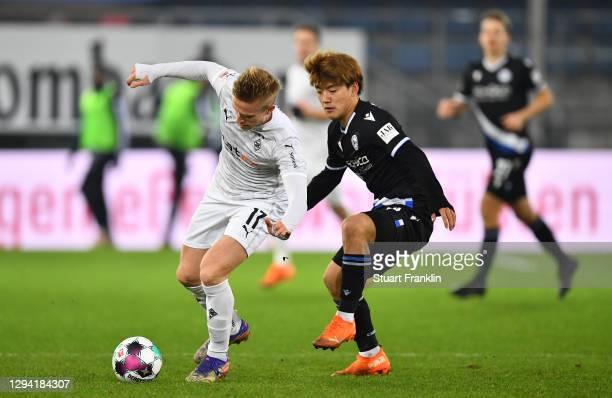 Oscar Wendt of Gladbach is challenged by Ritsu Doan of Bielefeld during the Bundesliga match between DSC Arminia Bielefeld and Borussia...