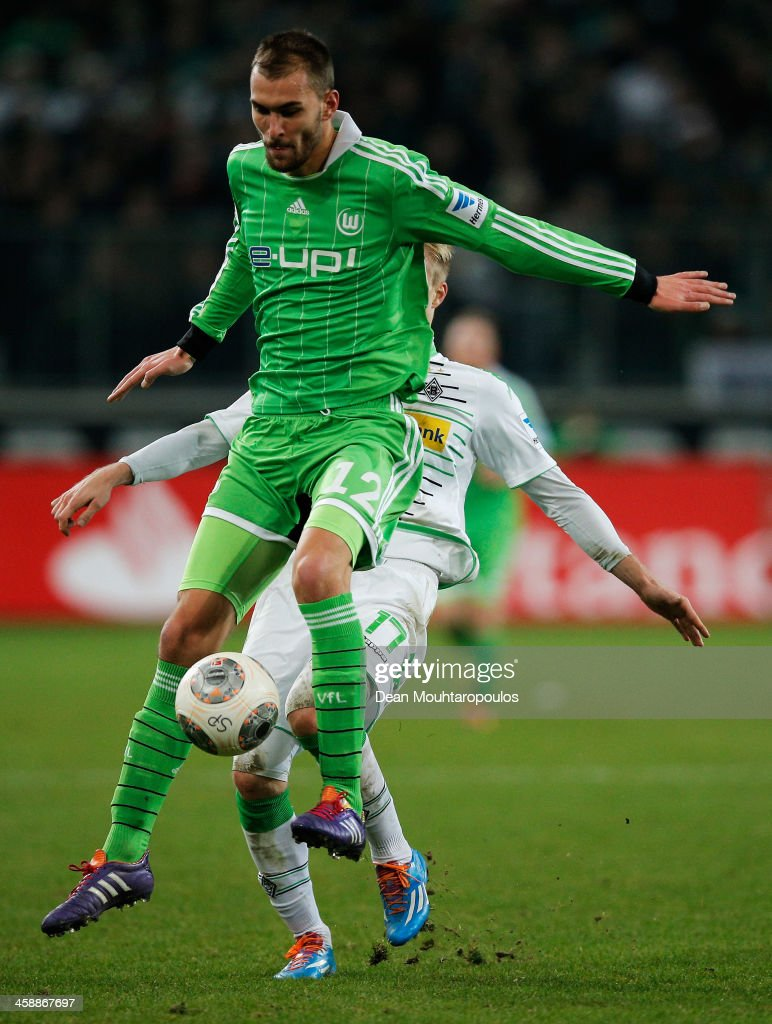 Oscar Wendt of Moenchengladbach and Bas Dost of Wolfsburg battle for the ball during the Bundesliga match between Borussia Moenchengladbach and VfL Wolfsburg held at Borussia-Park on December 22, 2013 in Moenchengladbach, Germany.
