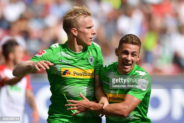 Oscar Wendt of Moenchengladbach celebrates his goal with Thorgan Hazard of Moenchengladbach during the Bundesliga match between FC Augsburg and...