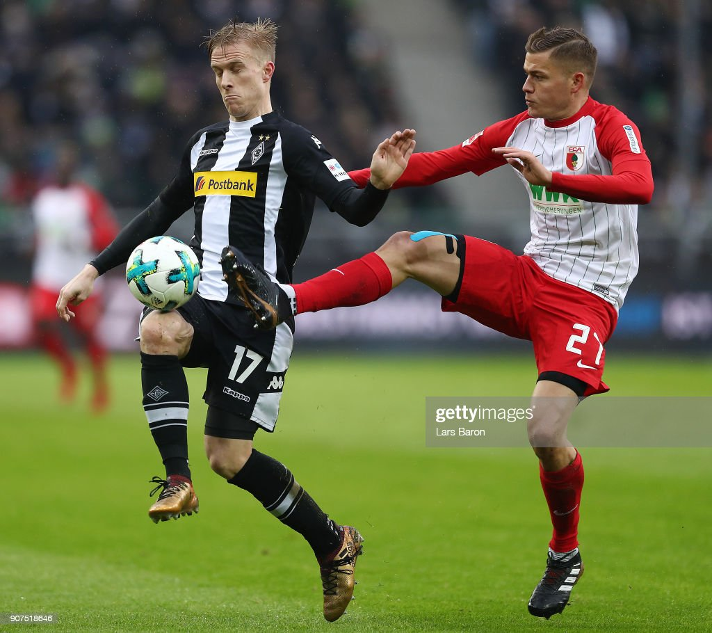 Oscar Wendt of Moenchengladbach (l) fights for the ball with Alfred Finnbogason of Augsburg during the Bundesliga match between Borussia Moenchengladbach and FC Augsburg at Borussia-Park on January 20, 2018 in Moenchengladbach, Germany. (Photo by Lars Baron/Bongarts/Getty Images)i