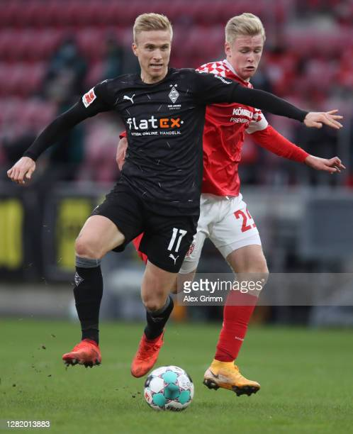 Oscar Wendt of Moenchengladbach is challenged by Jonathan Burkardt of Mainz during the Bundesliga match between 1 FSV Mainz 05 and Borussia...