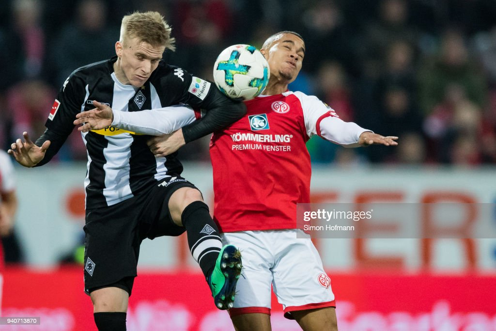 Oscar Wendt of Moenchengladbach jumps for a header with Robin Quaison of Mainz during the Bundesliga match between 1. FSV Mainz 05 and Borussia Moenchengladbach at Opel Arena on April 1, 2018 in Mainz, Germany.