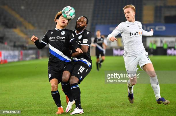 Oscar Wendt of Moenchengladbach reacts as Ritso Doan and Reinhold Yabo of Bielefeld go for the ball during the Bundesliga match between DSC Arminia...
