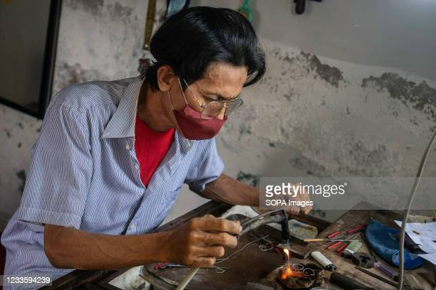 Osenk is connecting the joints of his silver jewelry. Kendari Werk jewelry is one of the many cultural treasures that Indonesia has. The meaning of...