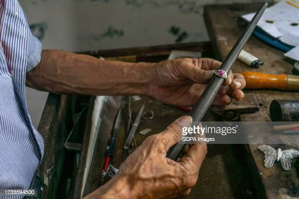 Osenk is tidying up his silver ring circle. Kendari Werk jewelry is one of the many cultural treasures that Indonesia has. The meaning of the word...