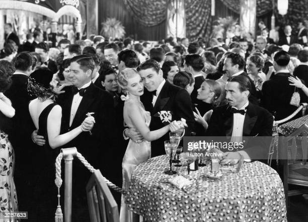 Osgood Perkins watches Paul Muni dancing with Karen Morley in a scene from 'Scarface' a film a clef based on the life of mob boss Al Capone...