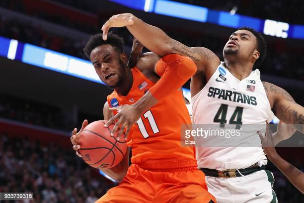 Oshae Brissett of the Syracuse Orange battles for the ball with Nick Ward of the Michigan State Spartans during the second half in the second round...