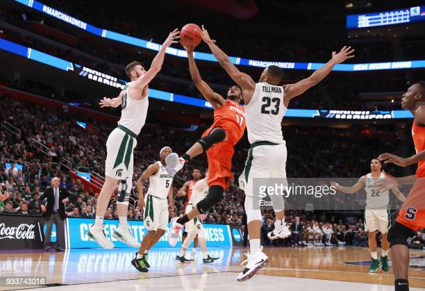 Oshae Brissett of the Syracuse Orange drives to the basket against Ben Carter and Xavier Tillman of the Michigan State Spartans during the second...